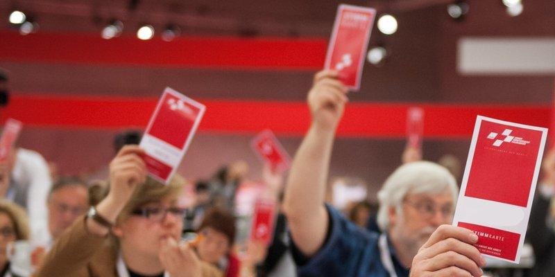 Saal mit Delegierten, die Stimmkarten heben