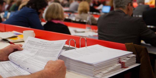 Großer Ordner auf dem Tisch eines Delegierten bei einem Kongress; Mann liest in Ordner